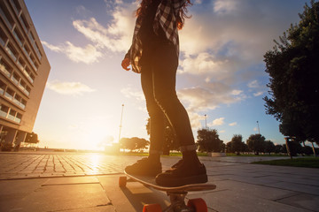 Young happy female riding on skate longboard outdoor