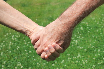 Holding hands outdoors.