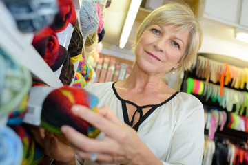 Lady holding ball of wool in craft shop