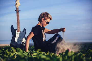 Portrait of young singer female with short hair wearing sunglasses seating on sea shore with electric guitar