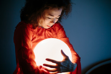 Young woman mixed race keep glowing ball lamp