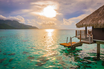 Evening with sunset in Moorea. Overwater bungalow on the side with breathtaking lagoon, French Polynesia