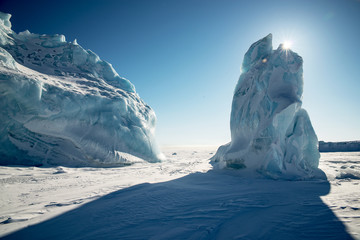 Two icebergs in the Arctic, a polar landscape. Because of one iceberg, a long shadow..