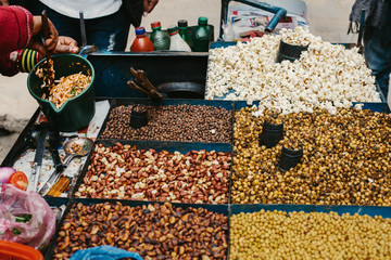 Street food in Asia, Nepal. Hands, cooking  traditional snack outdoor, popcorn, beans