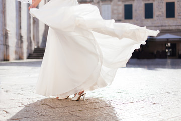 Bride is dancing. Bridal wedding dress or gown is white, light and flying. Girl has high heel shoes. Woman is in ancient italian stone town outdoor.