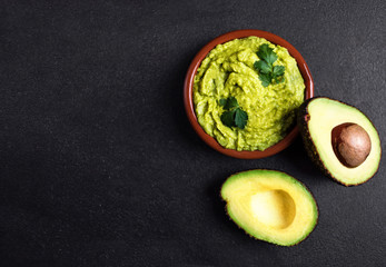 Guacamole sauce  in clay bowl with  cut half avocado on dark background. Top view with copy space.