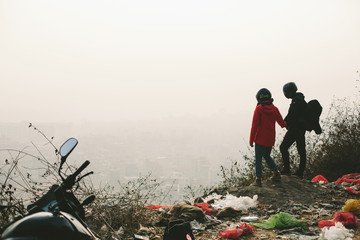 Couple of motor travellers wearing helmets staying on mountain top, looking on Kathmandu city. Garbage around, dusty view from the top