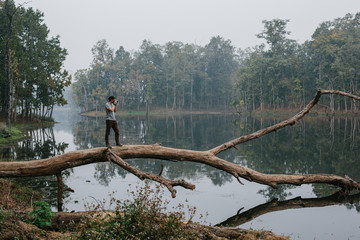 Traveller photographer standing on big tree and do pictures of tropical lake landscape