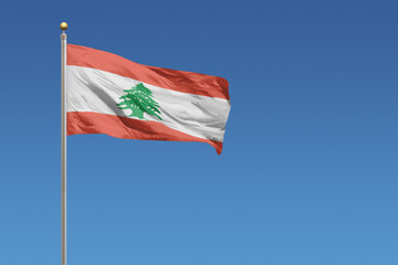 Flag of Lebanon in front of a clear blue sky