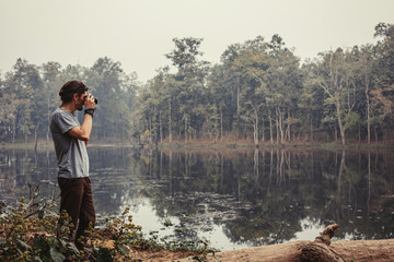 Traveller photographer standing and do pictures of tropical lake landscape by compact professional camera