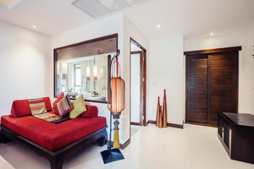 Modern bed room interior in expensive tropical hotel resort . Red sofa, big red lamp, wooden door and bathroom with big window