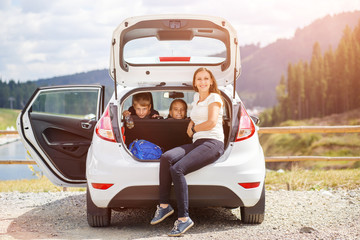Family traveling by car and having rest sitting in open trunk
