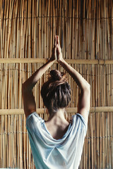 Woman doing yoga keep hands under her had, bamboo background, female back