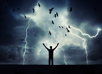Man silhouette on a storm background. Lord of the lightning. Background on the theme of survival, religion, philosophy, psychology.