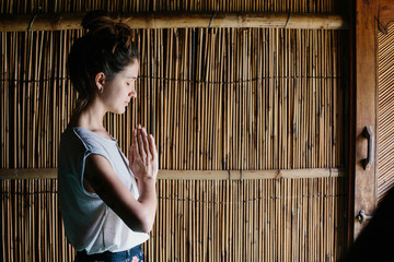Woman doing yoga keep hands together, bamboo background