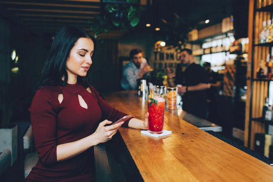 Nice picture of beautiful girl sitting at the barman's stand in the club and looking to the phone. She puts her left hand on the glass with cocktail. Barman and another guy are looking to her.