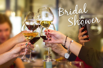 Female hands hold glasses of wine. Bridal Suite. A party of girls
