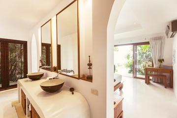 Bathroom and bedroom interior in luxury villa. Big windows, glass door to veranda outdoor
