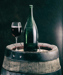 Glass of red wine and wine bottle on the oak wine keg.