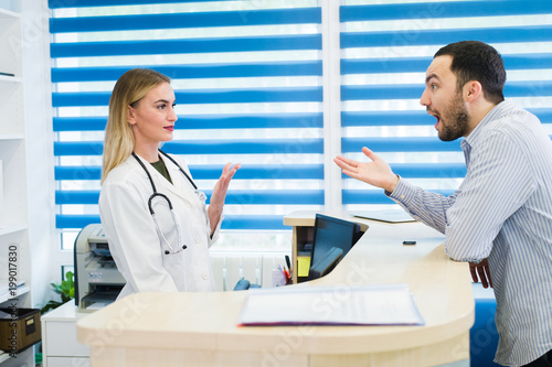 man talking to female receptionist at hospital