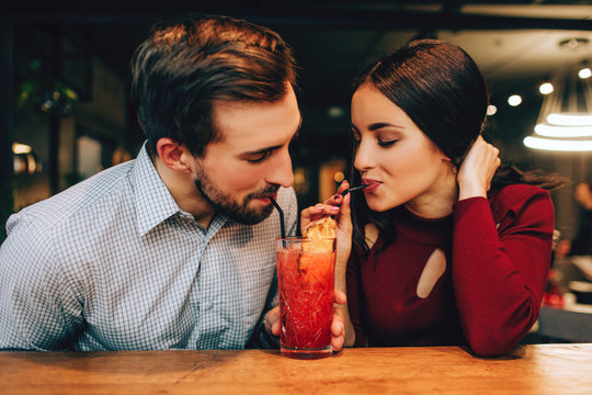 Nice picture of young couple sitting together and drinking red cocktail from the same glass at the same time. They look happy together.