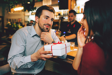 Boyfriend and girlfriend sitting together in restaurant. He has a present for her. She didn't expect that. She looks amazed and happy as so the guy is.