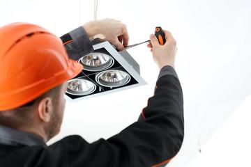 Fachowiec montuje oświetlenie.
