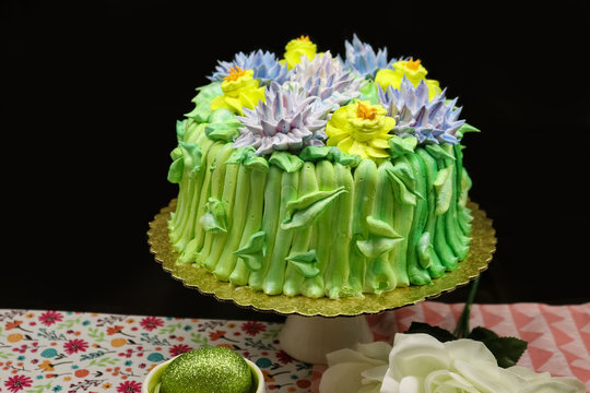 Colorful yummy springtime cake decorated with yellow and purple icing flowers