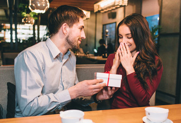 Guy is giving his girlfriend a gift in white box. She didn't expect that. He likes to make his beloved woman happy.