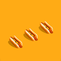 Hot dog photo Three hot dogs with mustard and pickled cucumbers are lying on a bright yellow background Trendy mockup for posters and banners with copy space