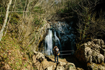 man with backpack taking pictures of the waterfall