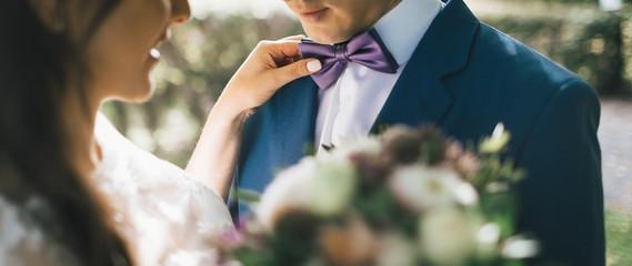 Close-up image Bride Adjusting Groom's Tie, sun backlit. Bride put hand on groom's shoulder. Artwork Wall mural