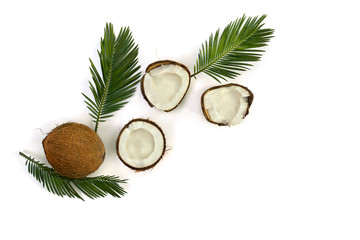 Coconut (Cocos nucifera) with halfs and palm leaves on a white background with space for text. Top view, flat lay.