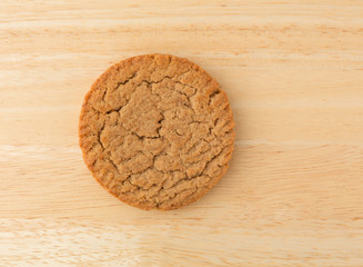 Top view of a single brown sugar and cinnamon cookie on a wood table.