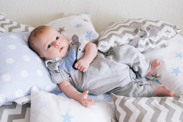Beautiful newborn baby lying in pillows  in delicate gray, blue, white tones