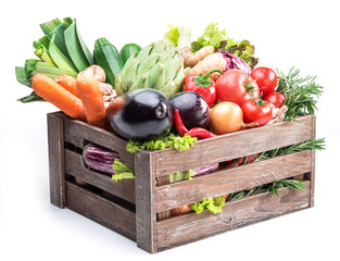 Fresh multi-colored vegetables in wooden crate.
