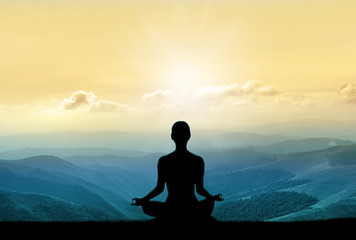 Yoga silhouette on the mountain in sunrays