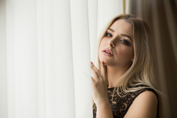 Elegant young lady in lace blouse posing near the window with curtain. Space for text