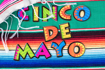 Cinco De Mao background with colorful mexican poncho serape rug.