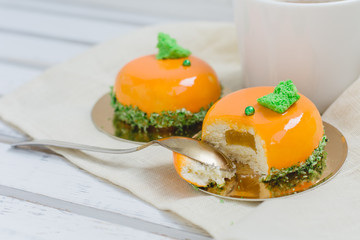 Bright orange mousse cakes and cup of coffee on white wooden tray