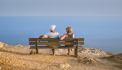 Happy middle-aged couple sitting on bench and enjoying beautiful view of the sea on cliff