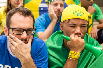 Group of fans watching a match and cheering brazilian team.