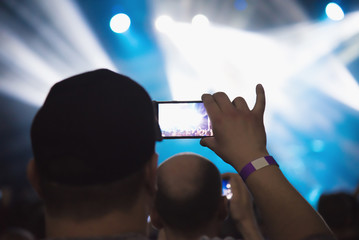 Video recording of the concert on the smartphone phone of the Beach party. Blue conceptual background of the youth party.