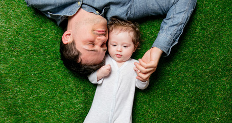 Young father and son lying down on green grass. Above view
