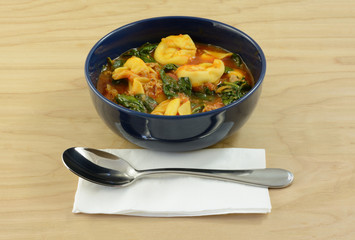 Cheese tortellini tomato stew soup with spinach and sausage in blue bowl with soup spoon and napkin