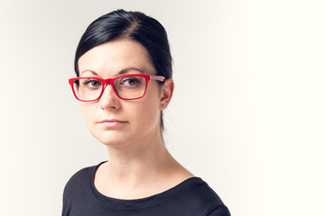 Portrait of a young woman with black hair and red glasses.