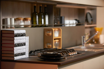 New modern kitchen interior with books and various kitchen utensils on the table. Luxury kitchen with the counter and stove