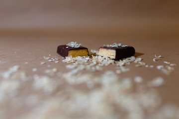 Closeup protein bar in the cut sprinkled with rice flakes on the baking paper, Teflon paper, Diet snacks, sports nutrition. Whey protein powder and chocolate protein bar on wooden background.