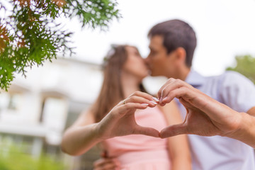 Closeup of couple making heart shape with hands and kissing
