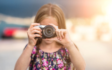 Beautiful little girl with camera takes a picture, summer outdoor